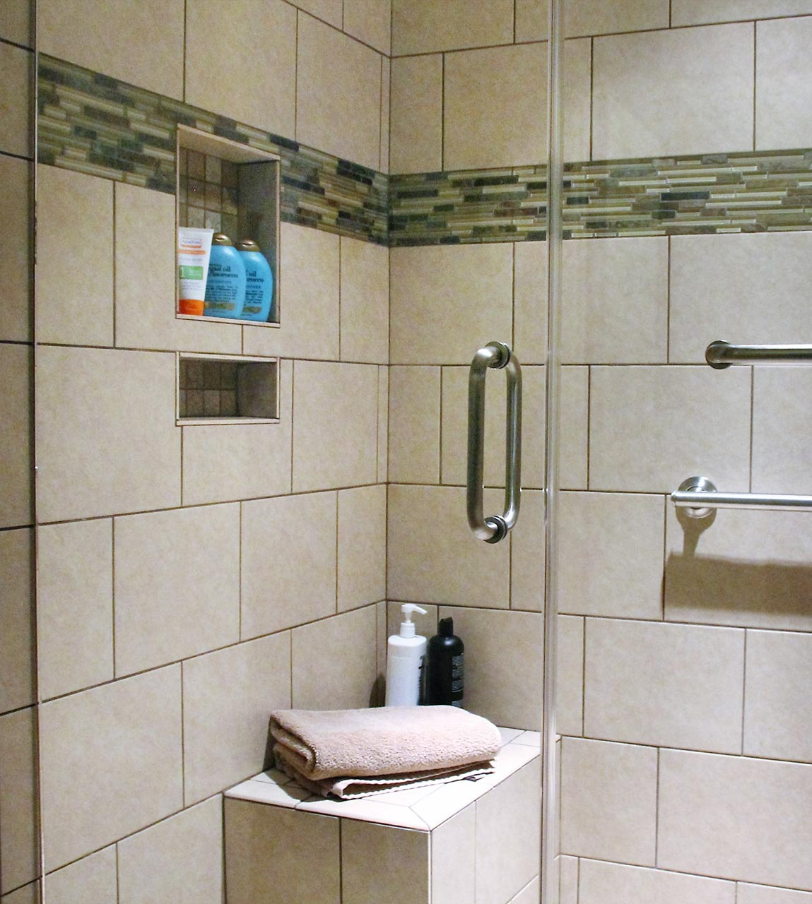 Close-up of new shower nooks and incorporated tile seat
