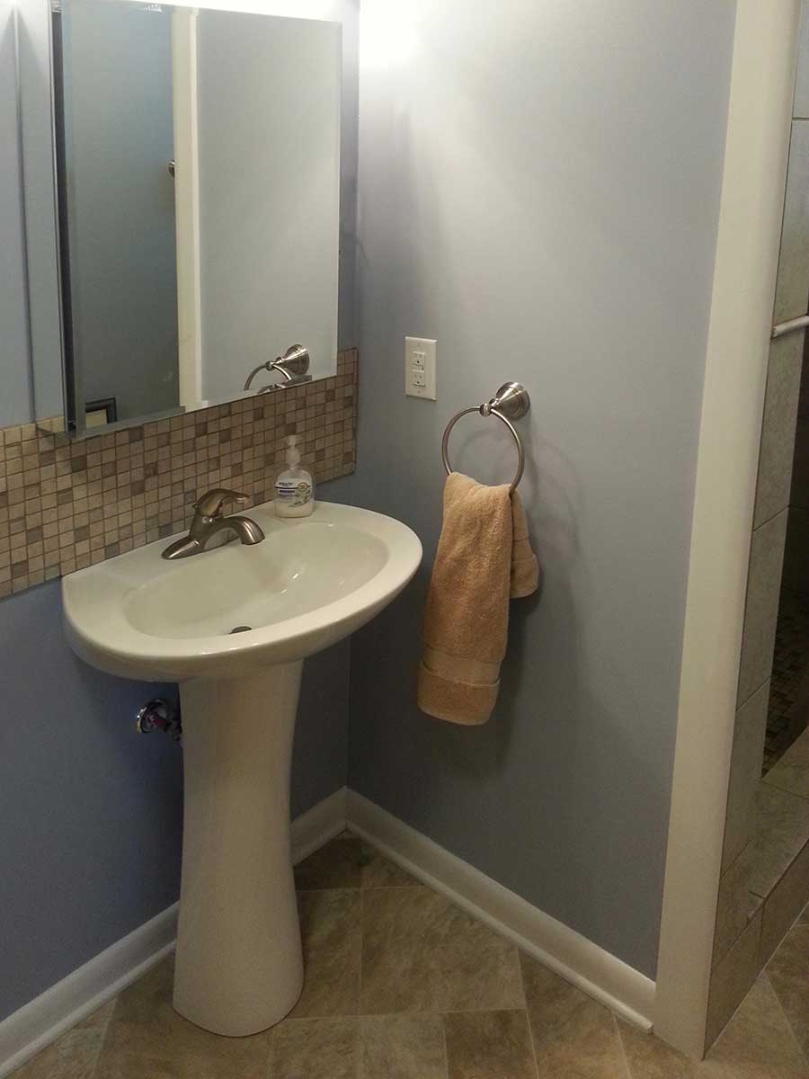 Small, freestanding sink and custom tile after bathroom remodeling