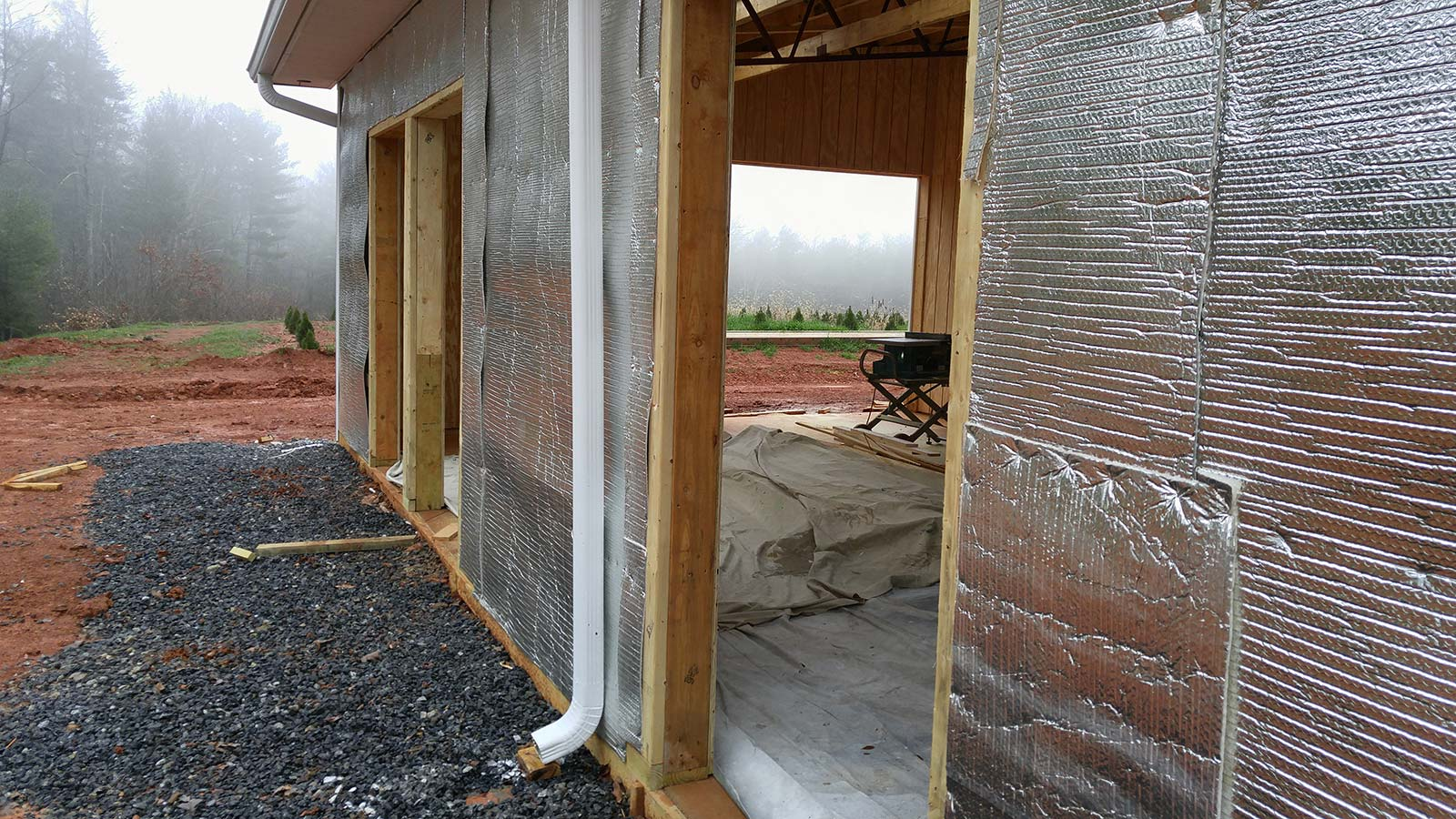 View of insulation being added to outside of horse barn