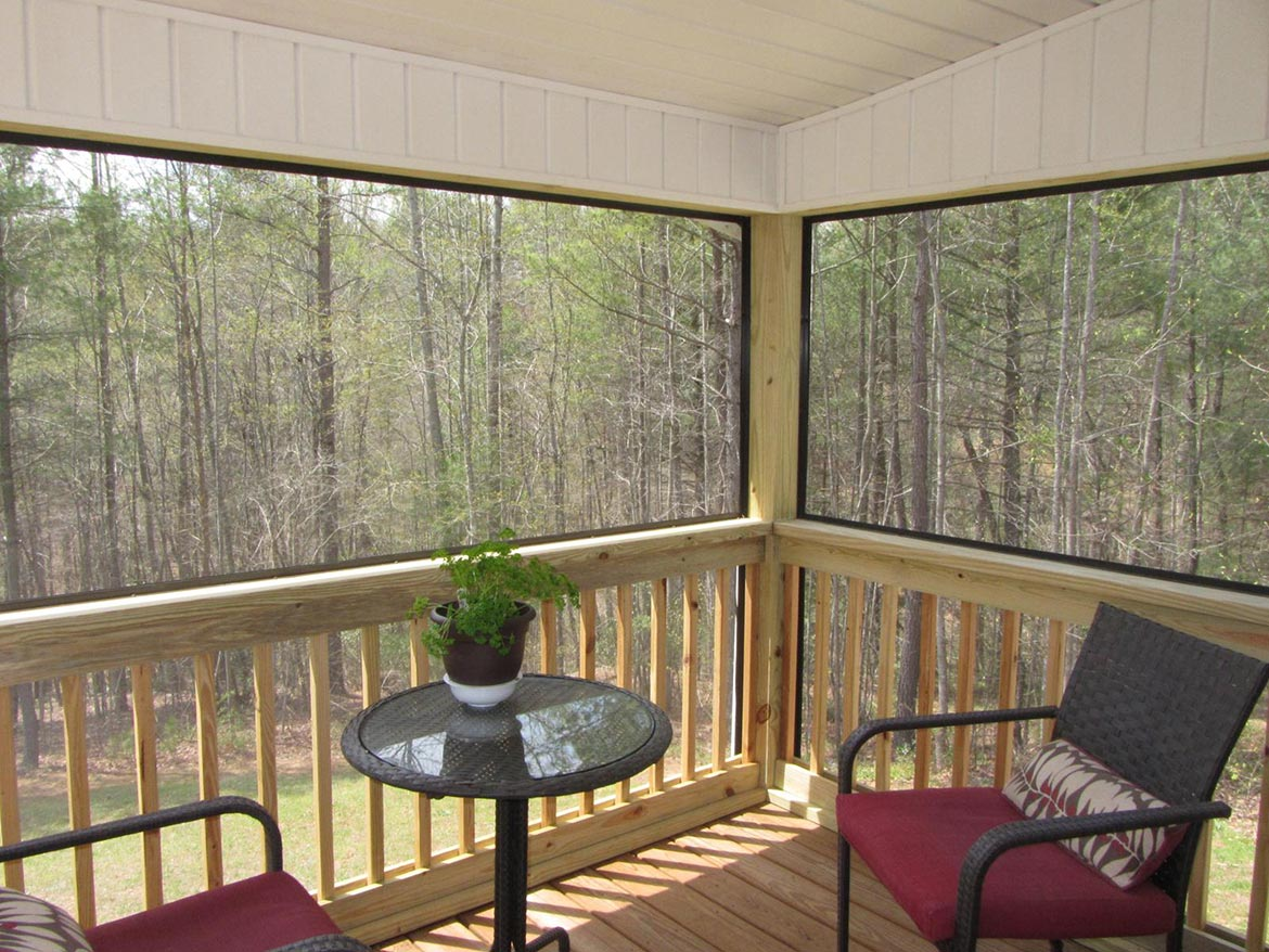 Inside screened in porch viewing wooded yard